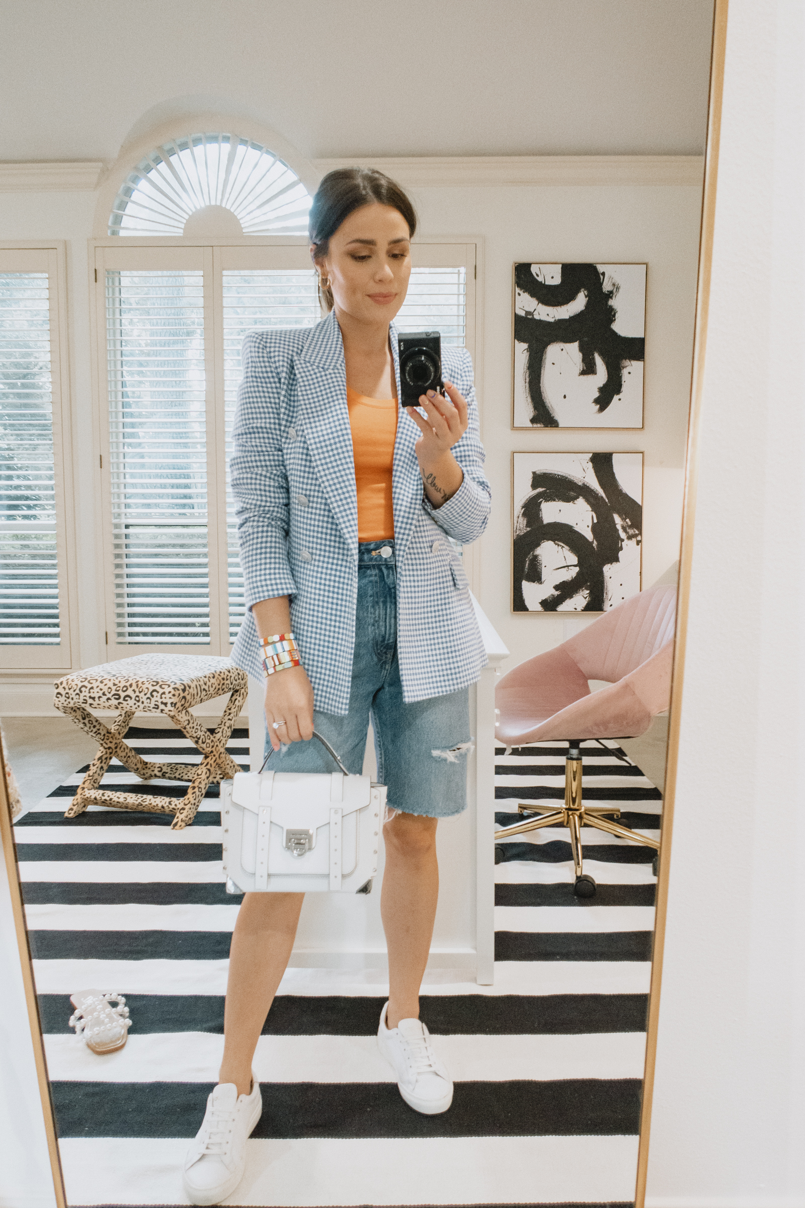 Elly Brown wears black bermuda denim shorts with white sneakers and a blue gingham blazer