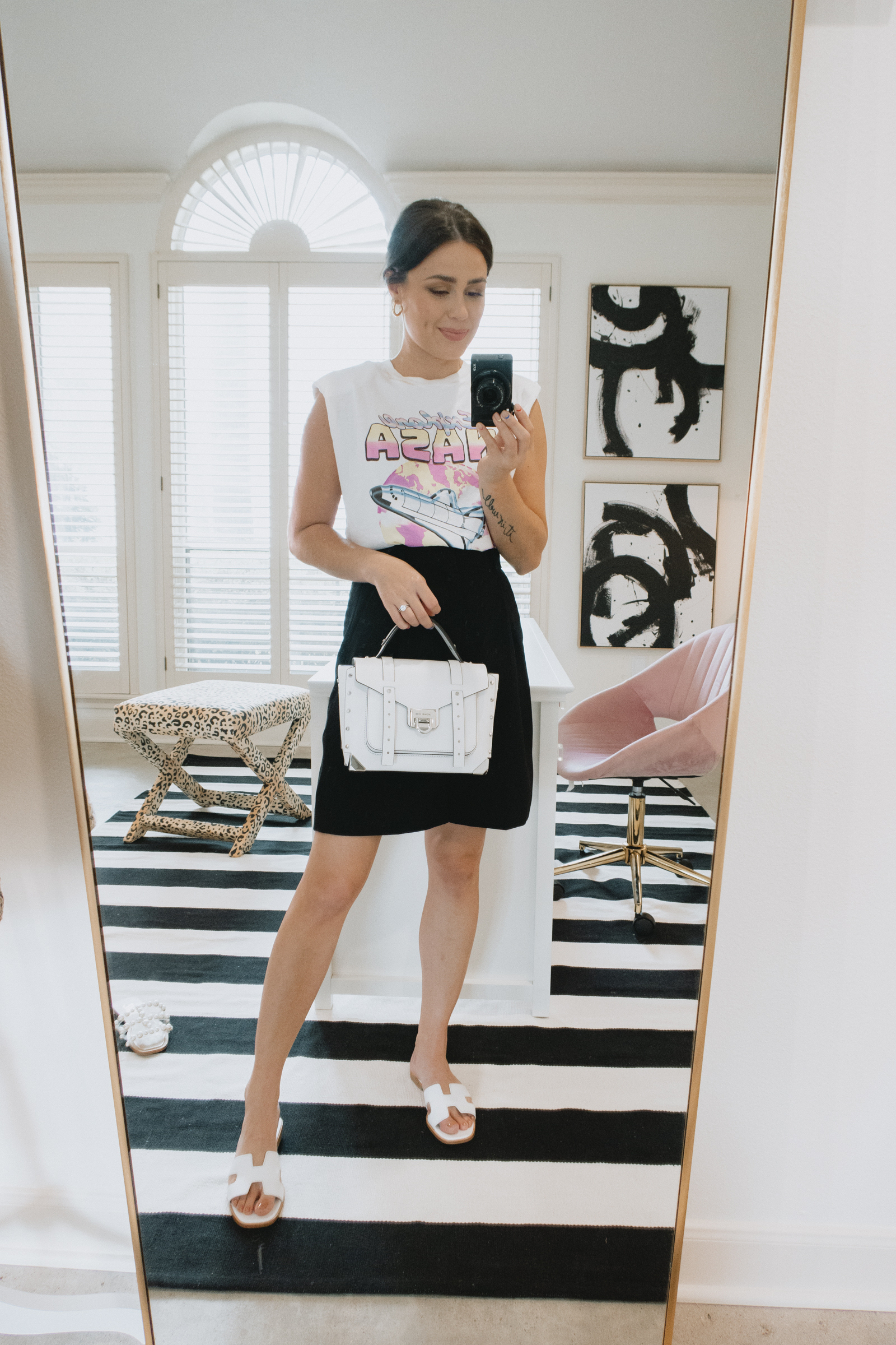 Elly Brown wears bermuda shorts with a graphic tee and Steve Madden white slide sandals