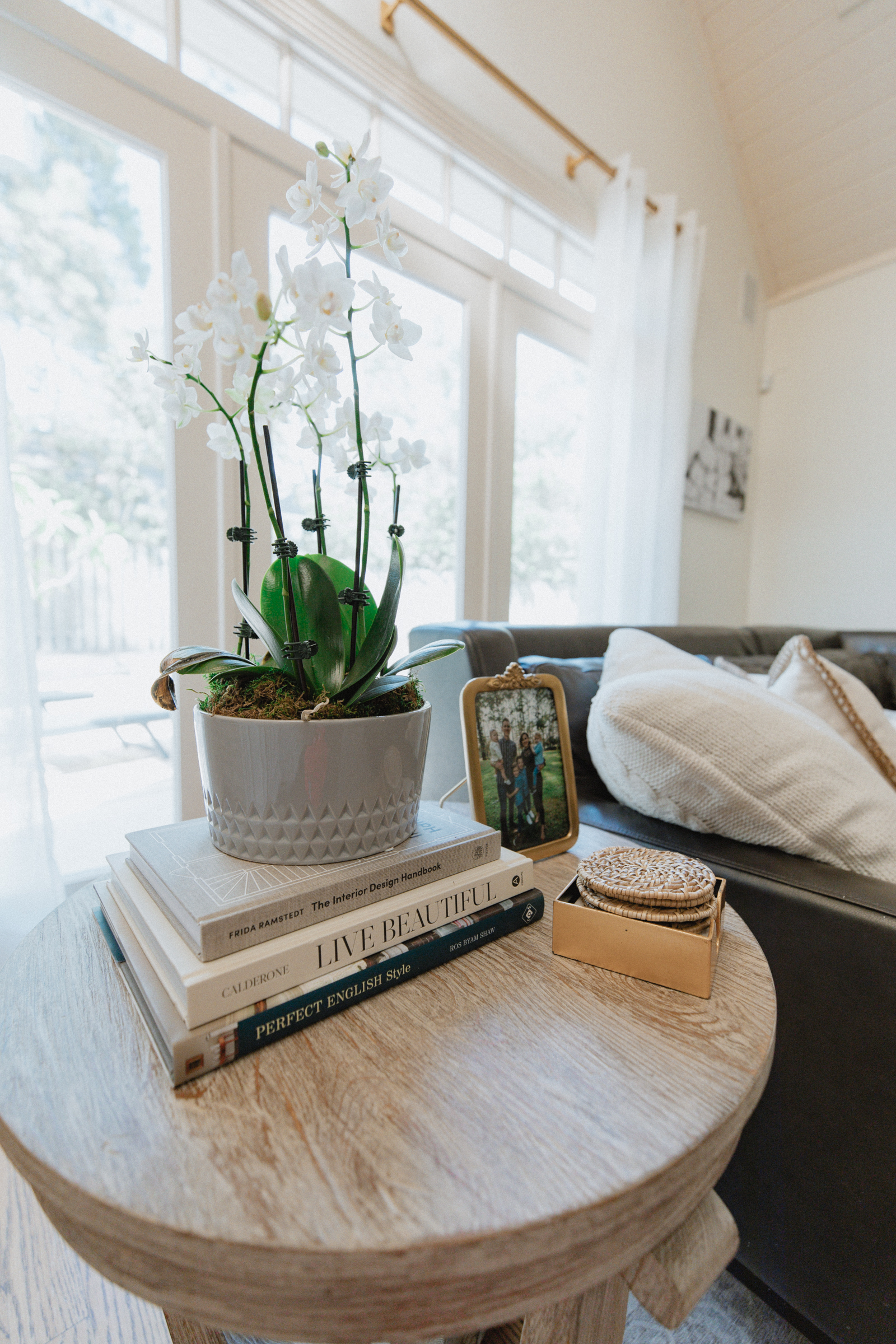Another close up of side table with potted orchid with family picture part of wayfair living room reveal