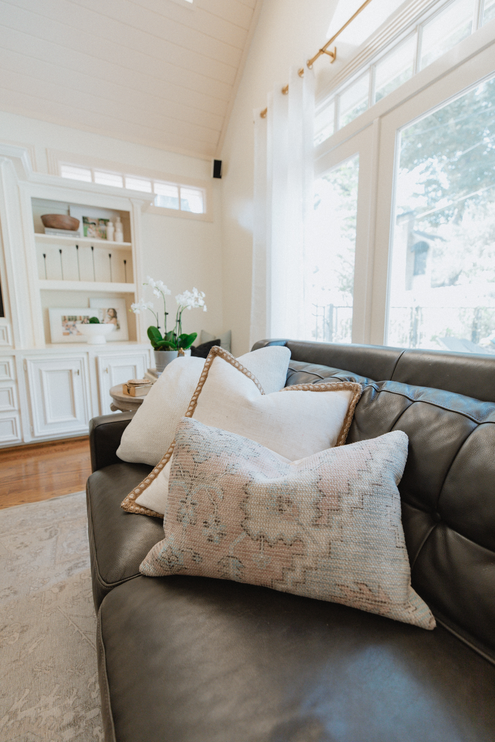 Three decorative pillows on leather couch part of wayfair living room reveal